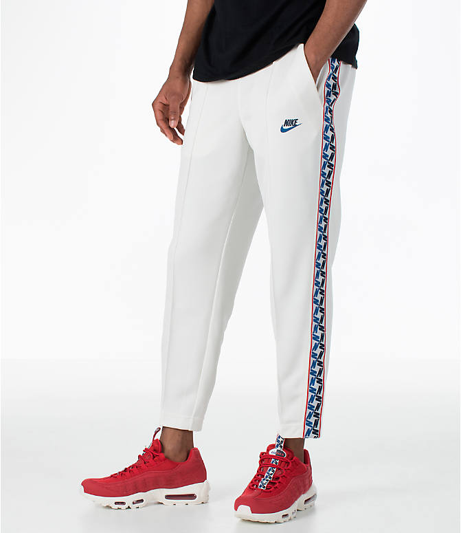 Front view of Men's Nike Sportswear AM Taped Track Pants in Sail