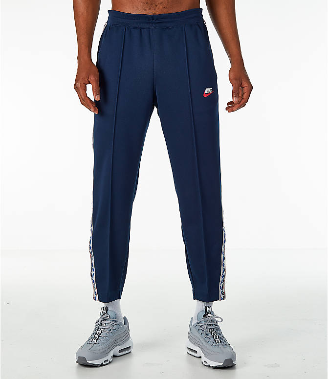 Front Three Quarter view of Men's Nike Sportswear AM Taped Track Pants