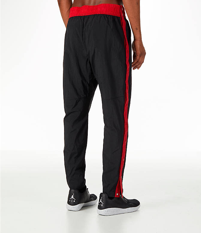 Back Right view of Men's Jordan Sportswear Rings Track Pants in Black/Gym Red