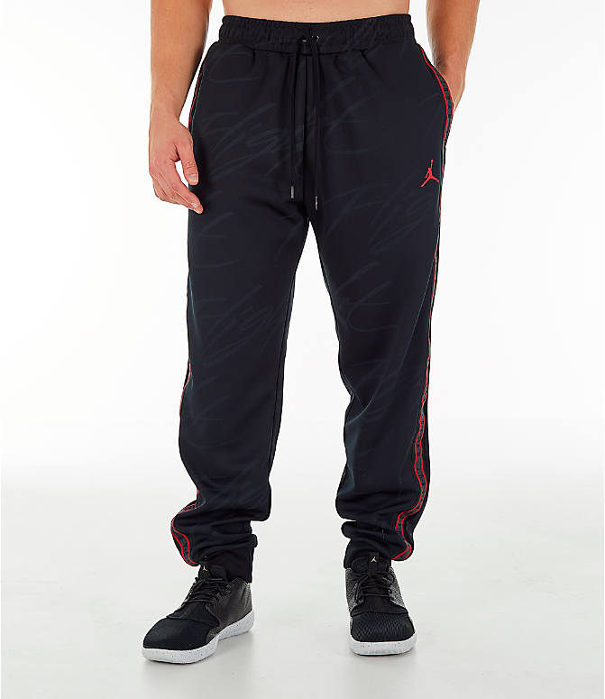 Front Three Quarter view of Men's Jordan Jumpman Graphic Track Pants in Black/Gym Red