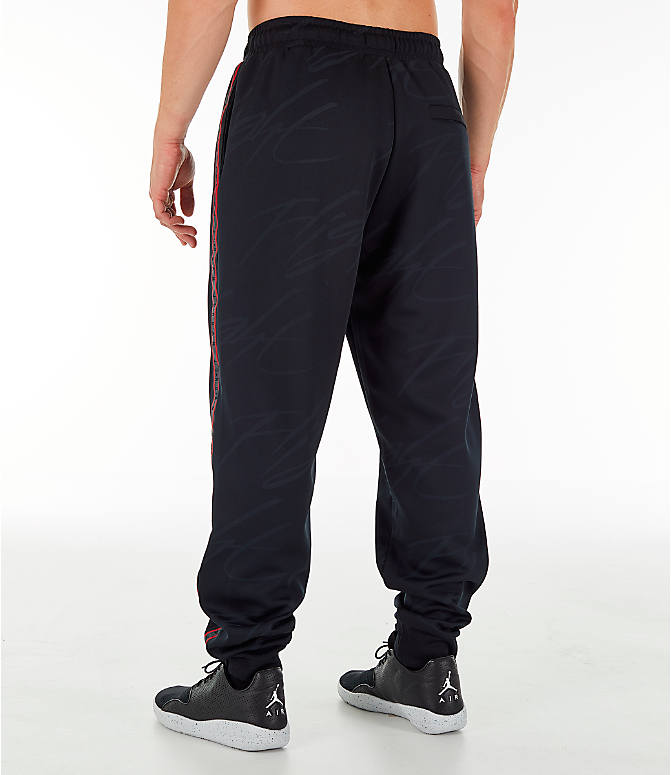 Back Left view of Men's Jordan Jumpman Graphic Track Pants in Black/Gym Red