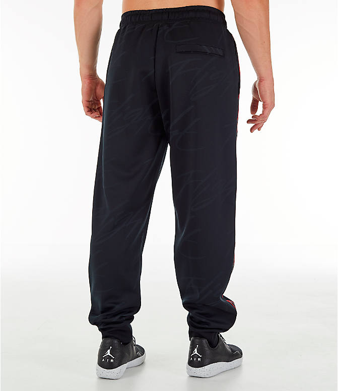 Back Right view of Men's Jordan Jumpman Graphic Track Pants in Black/Gym Red