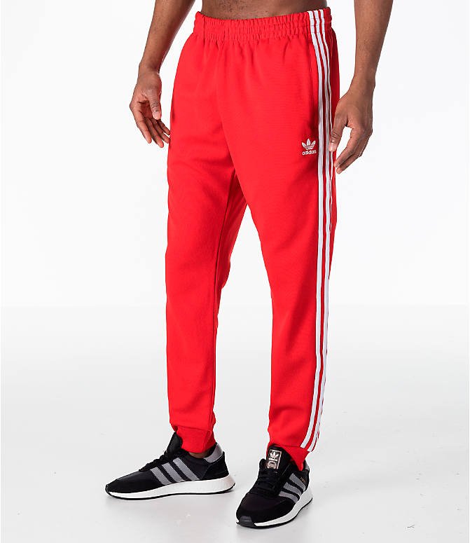 Front Three Quarter view of Men's adidas Originals adicolor Superstar Track Pants in Red