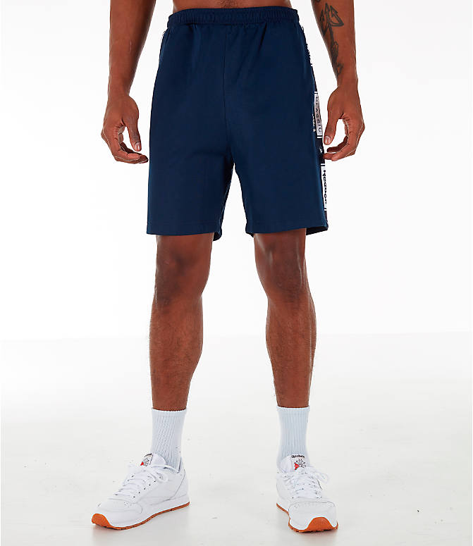 Front Three Quarter view of Men's Reebok Classics Taped Track Shorts in Collegiate Navy